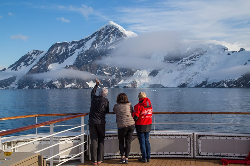 Three guests stand at the front observation deck of a luxury small ship staring at the icy mountain landscape of Antarctifca