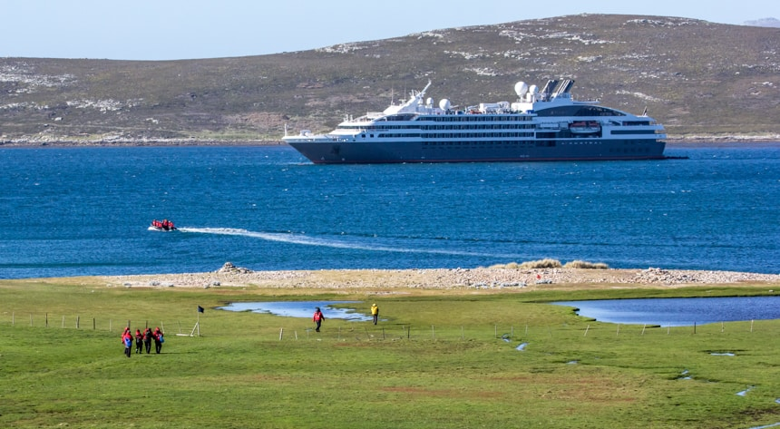 L'Austral, a luxury ship is floating in the blue ocean water as a group of people in red parkas walk towards the shore from a bright green grassy meadow
