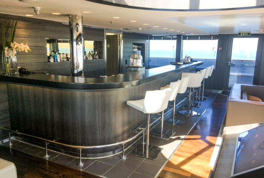 The bar area aboard L'Austral and her fleet of luxury ponant sister ships. grey curved counter top with white leather bar seats with silver accents are surrounded by glass windows to an outside viewing area.