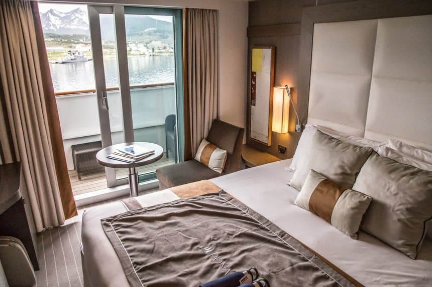 A cabin inside L'Austral and her fleet of luxury ponant sister ships. Neutral color pallet of white grey and golds are used throughout. A white leather tall headboard sits above the king bed, next to a small accent chair and coffee table. A sliding glass door leads to a private balcony