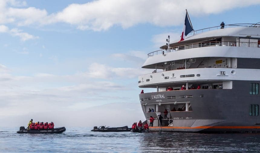 At the stern or back of the luxury ship L'Austral, black inflatable skiffs boat up to a landing dock where passengers in red parkas disembark and get back aboard the ship.