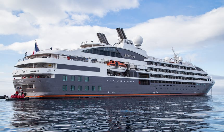 Floating on the blue ocean on a blue cloudy day, luxury ship L'Austral has a blue hull with red stripe, with 4 stories of white decks with private balconies.