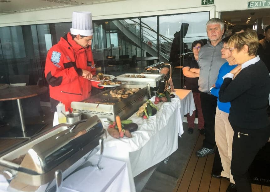 Aboard luxury small ship L'Austral a chef wearing a red parka and tall chefs hat stands behind an outdoor BBQ table and serves food to guests standing in line