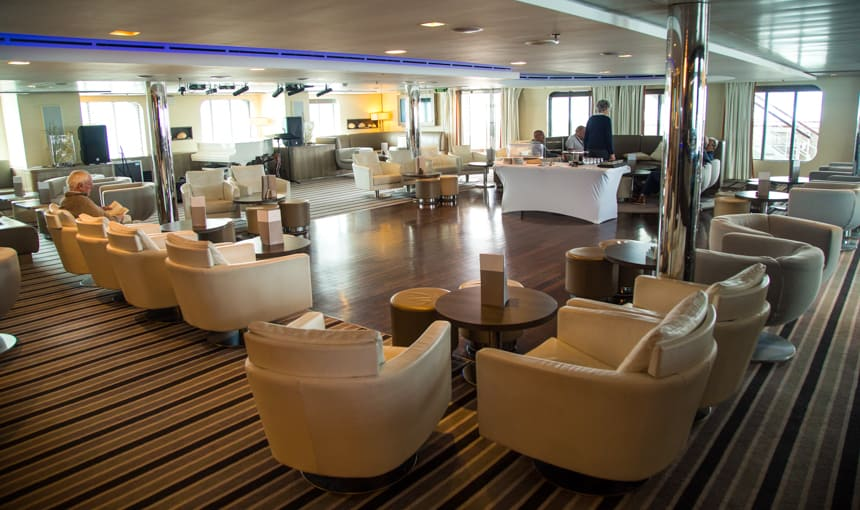 A lounge seating area aboard L'Austral and her ponant luxury sister ships. surrounded with large glass windows cream, beige and brown leather arm chairs are set facing the windows with ottomans and coffee tables on top of striped carpet and wooden square dance floor.
