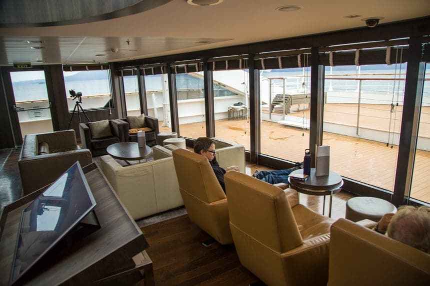 A lounge seating area aboard L'Austral and her ponant luxury sister ships. surrounded with large glass windows cream, beige and brown leather arm chairs are set facing the windows with ottomans and coffee tables.