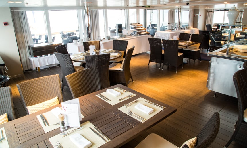 One of the restaurants and dining room options aboard L'Austral and her ponant luxury sister ships. surrounded with large glass windows brown tables and chairs are set around a centered steel buffet area.