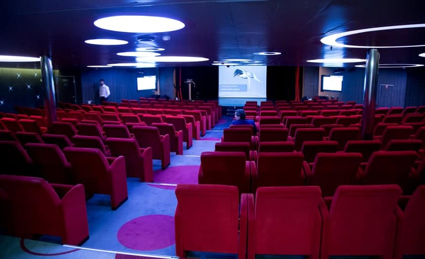 the theater inside L'Austral and its sister ships with rows of red comfy movie theater seats lined in a circular fashion, facing the front stage, the lights are dimmed and a screen at the frotn is showing an educational video. circular lights on the ceiling match the large circular dot pattern on the carpet.