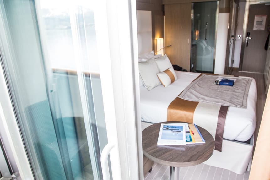 Standing outside on a private cabin balcony looking in is a cabin aboard L'Austral luxury ship, an accent chair and coffee table, queen bed with white linen.