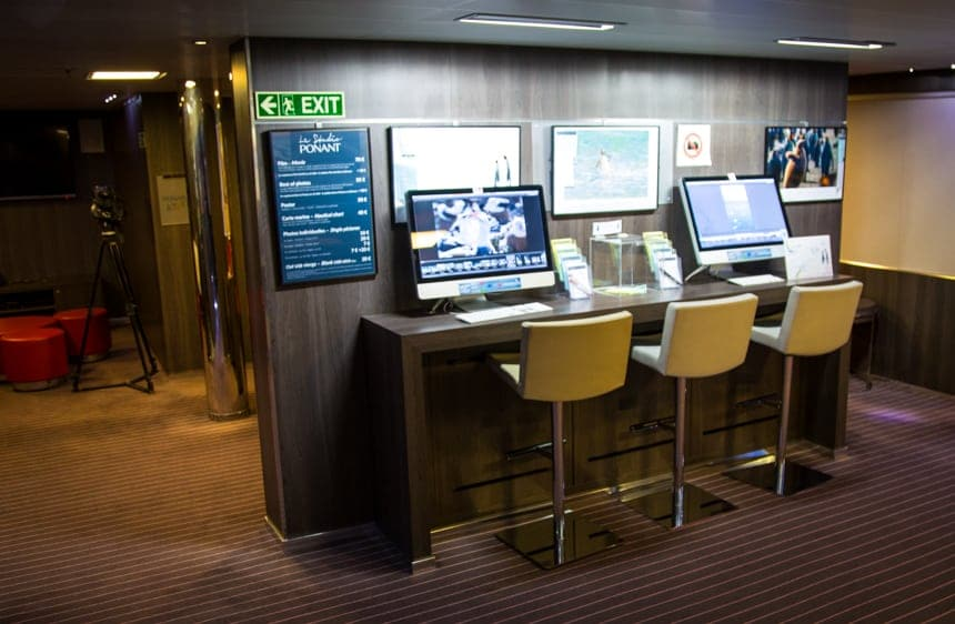 The media center aboard L'Austral luxury ship, three bar height chairs are seated in front of computer screens,