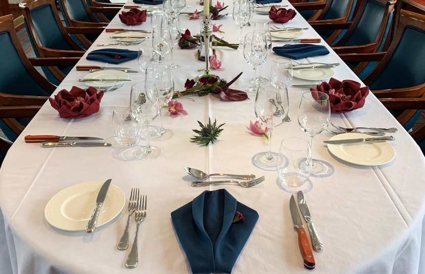 an empty dining table aboard Spirit of Scotland barge set with place setting and utensils, with a white table cloth and maroon napkins folded into the shape of a flower.