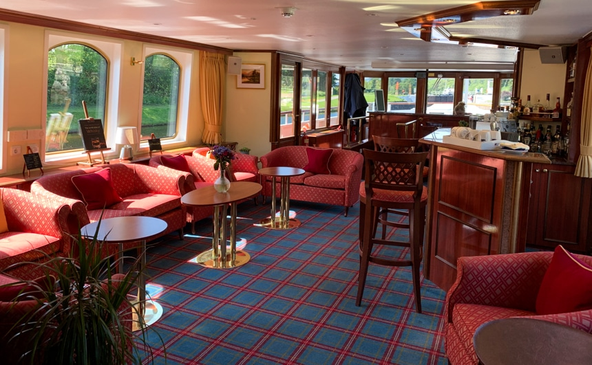 Inside the lounge aboard Spirit of Scotland Barge, plaid carpets sit underneath a set of red love seats and arm chairs, with wood and gold coffee tables, surrounded by glass windows.