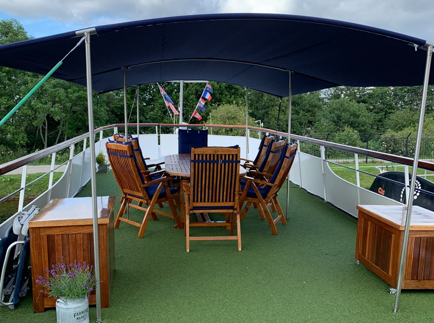 Covered dining terrace on the rooftop deck of Spirit of Scotland barge with short green turf carpeting, and a wooden table and chairs.