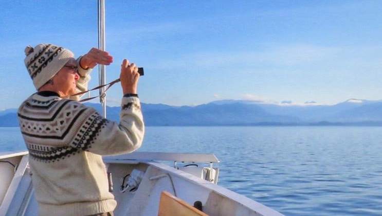 Traveler dressed in warm clothes with binoculars stands on bow of a small ship during the Alaska Bear Country Wilderness Expedition.