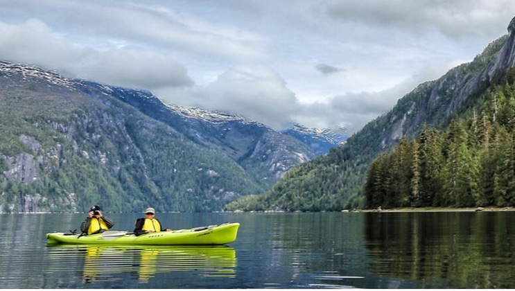 Tandem kayakers in a bright green kayak practice their Alaska cruise photography in calm waters with mountains in the background on a partly sunny day.