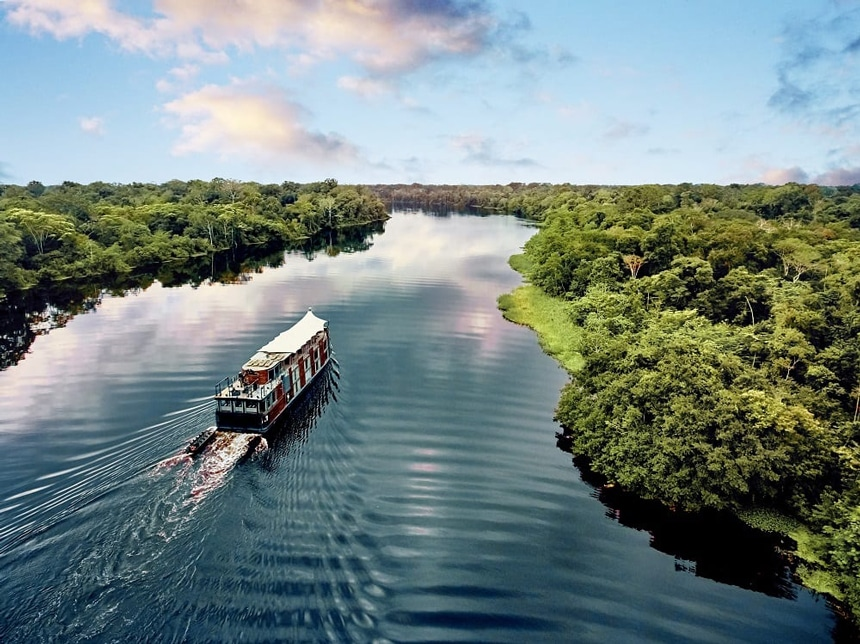 Peruvian amazon river boat the Aria, floats down the amazon rover, flaked on either side by lush green jungle.