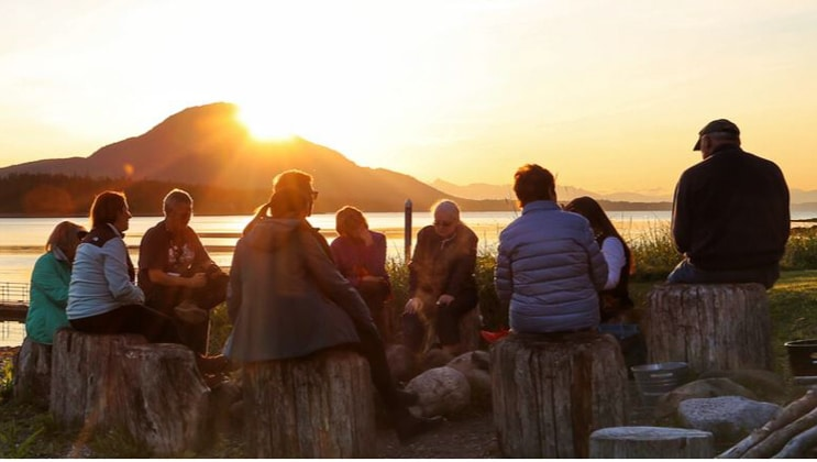 Group of Alaska travelers sits around a large campfire at sunset during a feast at Fin Island Lodge, during the Alaska Coastal Discoveries & Culture Cruise.
