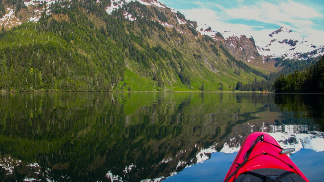 View from sitting inside a red kayak on glassy water with reflections of green & snowy hillsides during an Alaska small ship cruise.