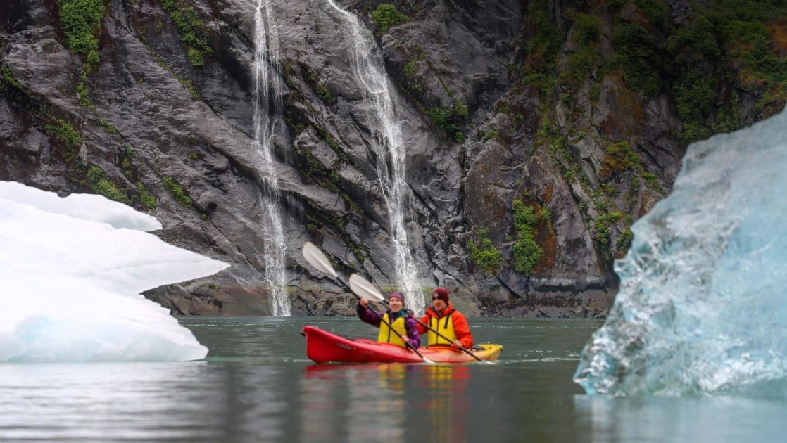 Two travelers paddle a double kayak between icebergs and in front of a waterfall on an Alaska small ship cruise.