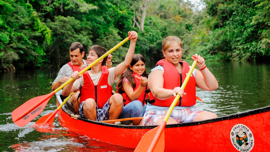 Family smiling while paddling a red canoe on a river in the jungle in Belize on a tour.