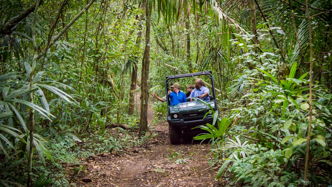 A small group of people on a four wheel drive off roading rainforest tour in Belize.