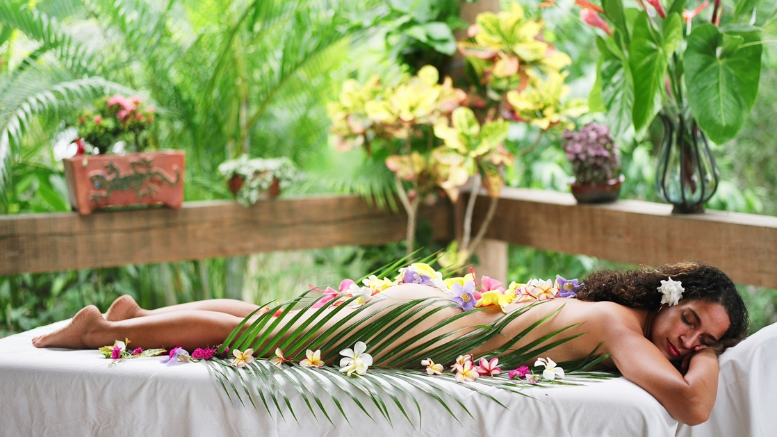 Woman peacefully relaxing on a massage table receiving a spa treatment in a private outdoor area surrounded by jungle foliage and flowers in Belize.