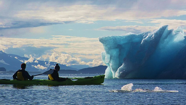 A pair of tandem kayakers paddles up to an icy blue iceberg bit during the Glacier Bay Outer Coast Expedition.