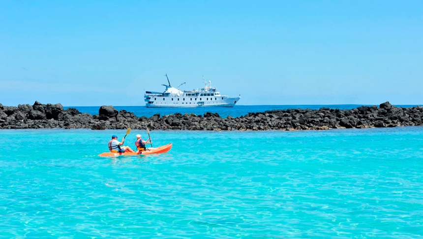 In the Galapagos Islands two kayakers paddle their kayak in teal ocean water, floating in the distance is small ship La Pinta.