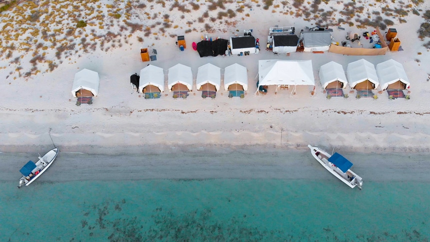 An areal photo of luxury glamping camp in Baja. A row of tens sit ocean front as two boats float offshore.