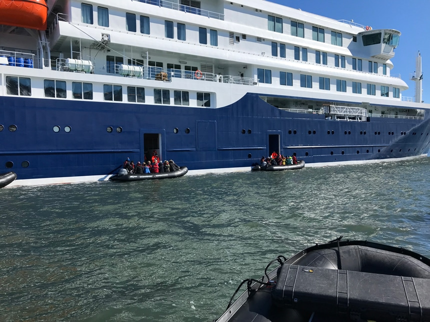 two black inflatable skiffs filled with people float on the water outside entry doors of the new polar ship Jassonious.