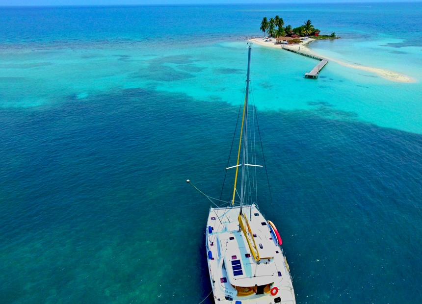 An aerial photo of a white catamaran as it floats in the crystal clear blue waters of Belize around a tiny sandy palm tree filled island