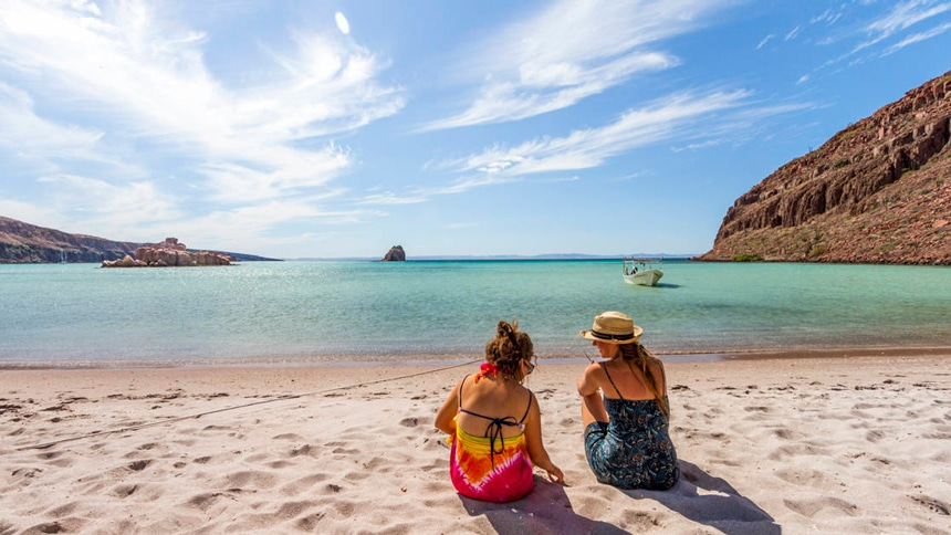 A bright sunny day in Baja two female vacationers sit on the sandy beach in front of the waters edge.