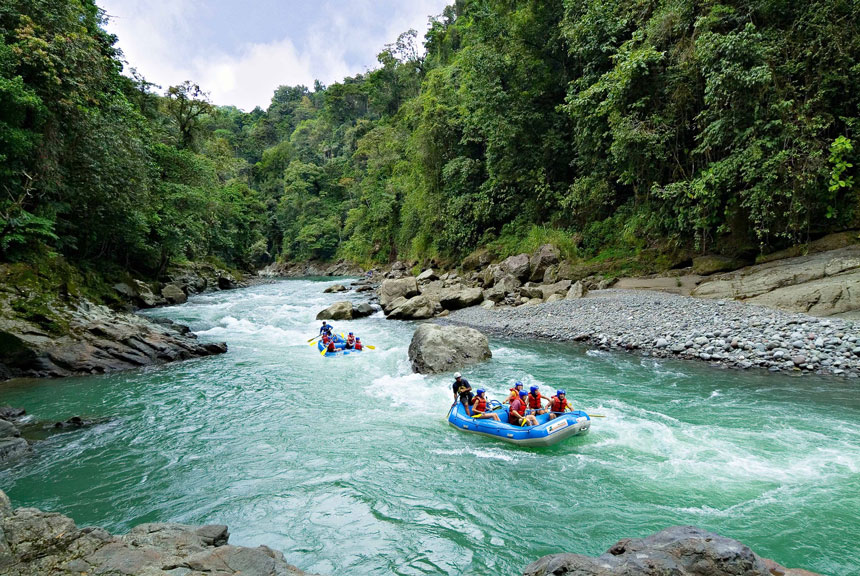 wearing helmets and life jackets two groups of river rafters float down a river in the lush rainforest of Costa Rica