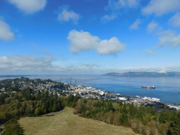 Aerial view of Astoria, Oregon, with rolling green hillside, blue sky, shipping vessel on a wide river & assorted buildings.