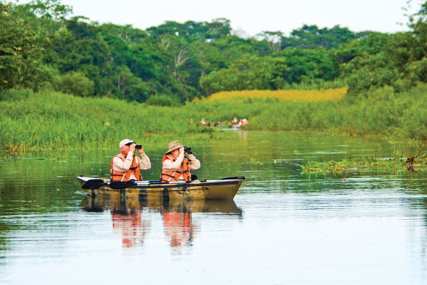 Amazon birders use binoculars from a tandem kayak to watch for wildlife in a calm tributary.