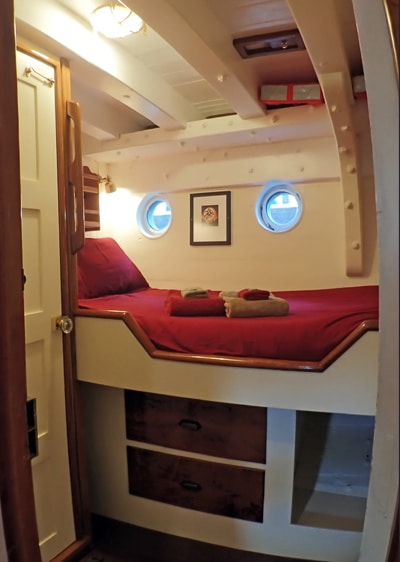 Cabin 2 aboard Catalyst, small ship in Alaska. Two porthole windows above a single mattress wrapped in red bedding and pillows.