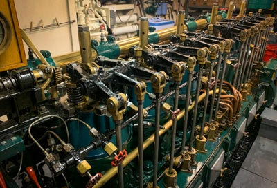 The engine room aboard small ship Catalyst, with a row of green and gold colored machinery parts