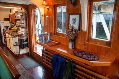 The galley aboard smalls ship Catalyst, brown glossy wood with shelfs, a seating area and small kitchen