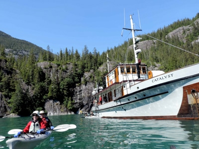 On a blue sunny day in Alaska the small ship Catalyst floats on blue water as two guests paddle a double kayak near by