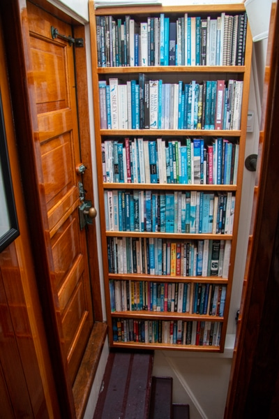 A book shelf filed with books sits at the top of a steep staircase leading to the lower deck of Alaska small ship Catalyst