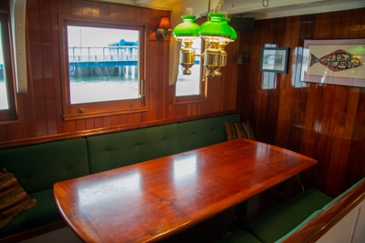 The main salon aboard Alaska small ship Catalyst. A long wood table with green bench seating and windows to the outside,