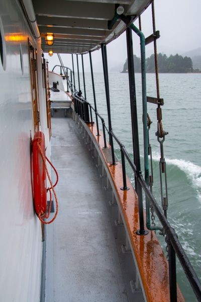 Looking out over a rainy Alaska landscape from the outer walk way that surrounds the main deck of Alaska small ship Catalyst.