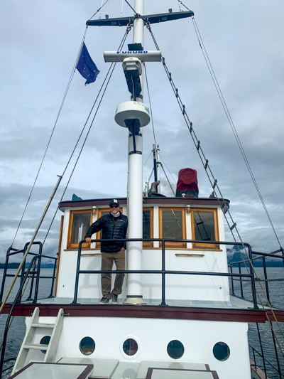 An Alaska cruise passenger standing on the top deck of the Catalyst small ship in front of the pilot house.