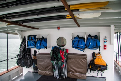 A covered deck aboard Alaska small ship catalyst, where adventure activity items like kayak paddles and lift jackets are stored.