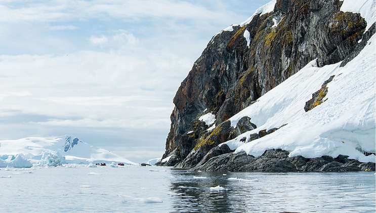 Zodiacs with Antarctica travelers sit in the distance, beside a small rocky mountain with snow.