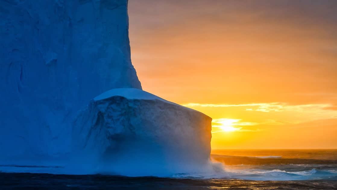 Orange sunset behind tall dark blue glacier seen during Le Commandant Charcot Ross Sea Expedition.