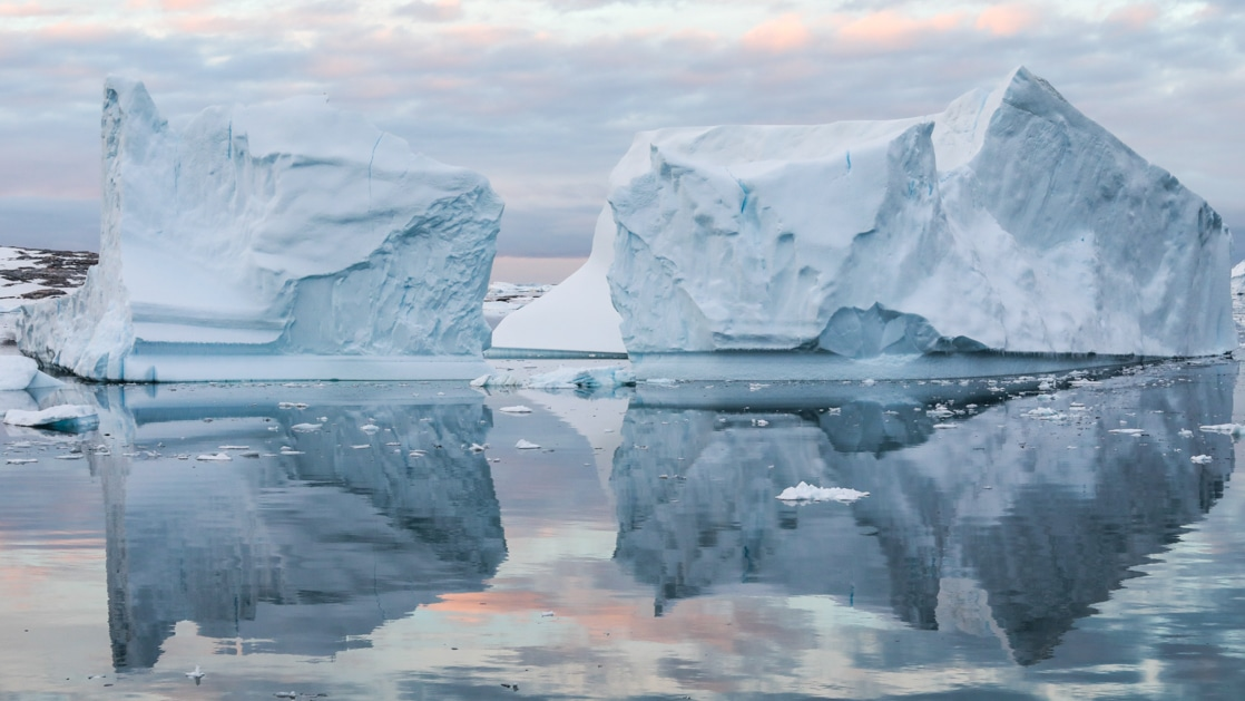 Large icebergs reflect in glassy Antarctic waters at dusk during the Le Commandant Charcot Ross Sea Expedition.