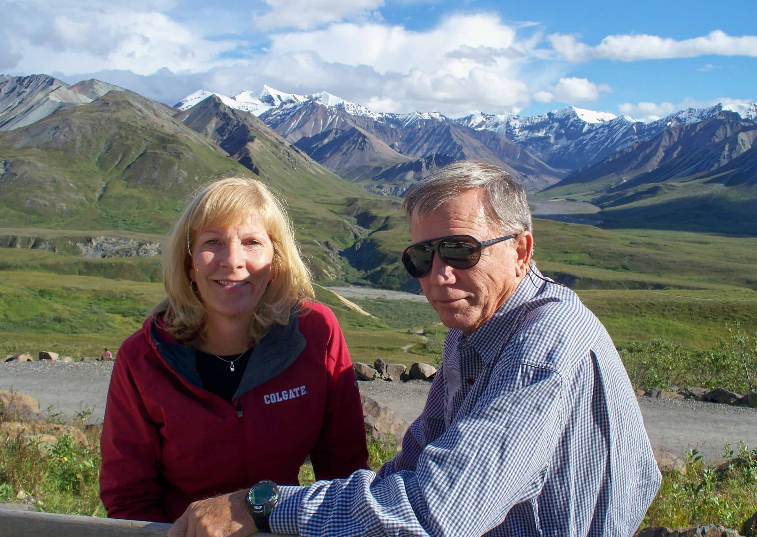 Happy couple enjoying a viewpoint of Denali National Park with green tundra & mountain range in the background.