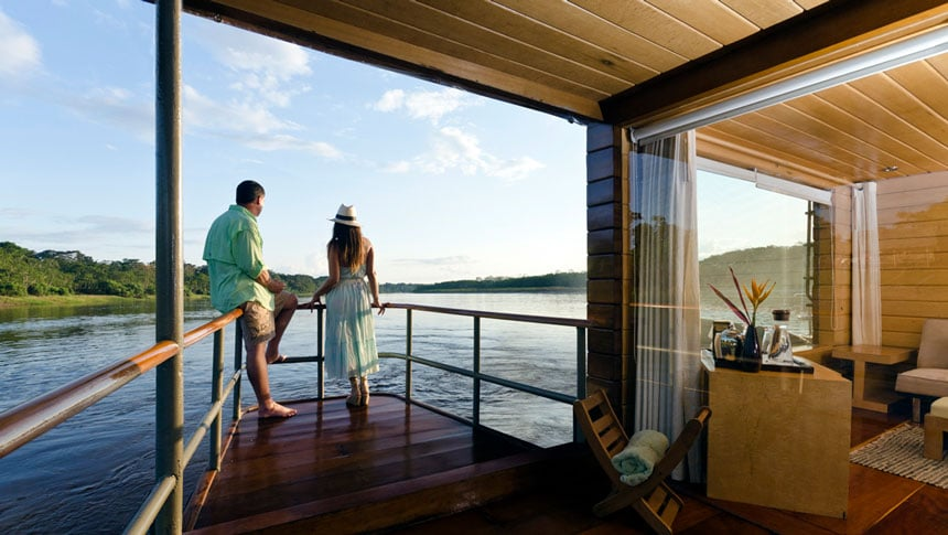 Woman & man stand on bow of private balcony on wooden Amazon riverboat as it cruises.