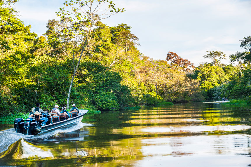 Amazon travelers & guide ride in an aluminum skiff boat along glassy water lined by jungle.