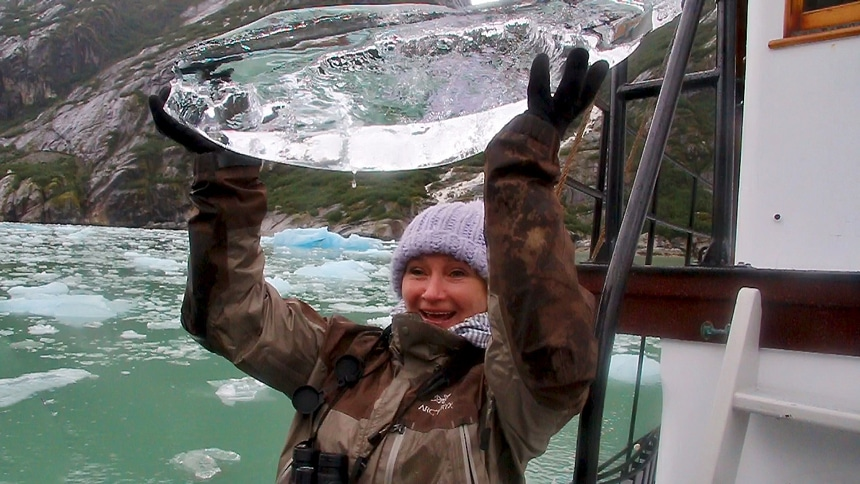 Aboard Catalyst in Alaska's Endicot Arm a female cruise guest lifts a large crystal clear piece of iceberg above her head